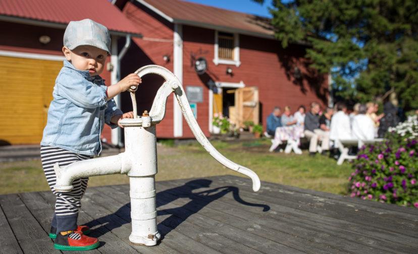Taaperoikäinen lapsi Havulan kartanon pihapiirissä, kaivon pumpun vieressä