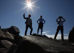 Kalliolla seisovat ihmiset kuvaavat yrityksen kasvua