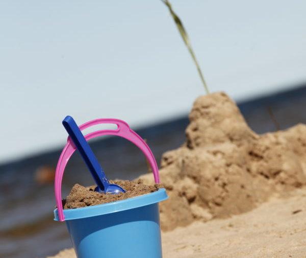 Uimarannalla hiekkalinna ja lasten ämpäri täynnä hiekkaa