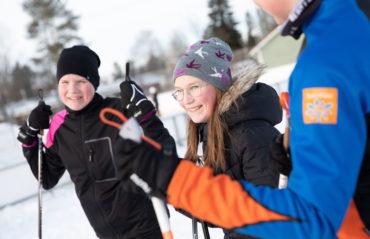 Kaksi nuorta tyttöä lähdössä hiihtämään talvisäässä nojaillen suksisauvoihin.