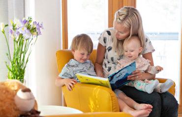 Äiti ja lapset lukevat kirjaa.