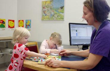 Lapsi pelaa palapelia terveydenhoitajan vastaanotolla