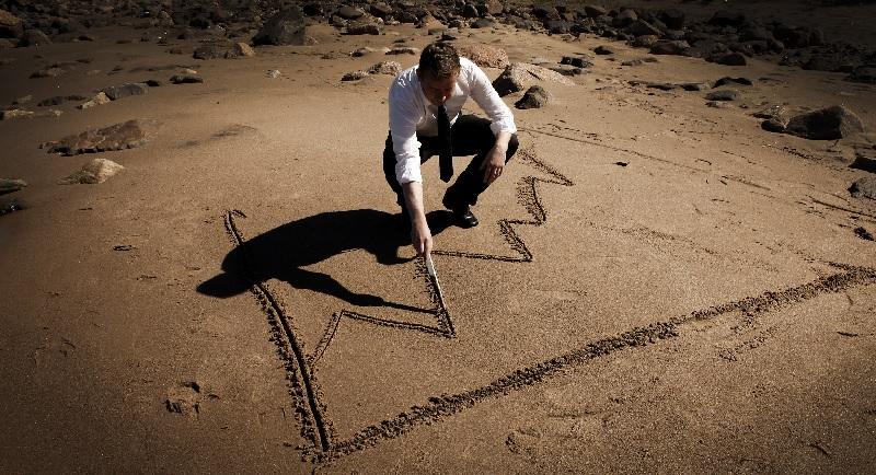 Mies piirtää hiekkaan nousevaa tuloskäyrää.