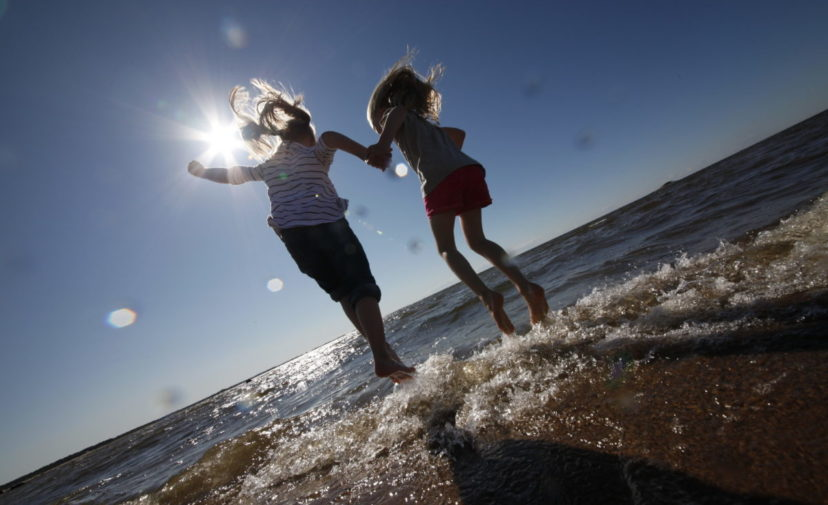Lapset juoksevat rantavedessä