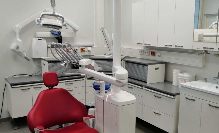 Täysin varusteltu hammashoitolahuone. Keskellä punainen hoitotuoli ja hammashoidon välineitä ja laitteita ympärillä.