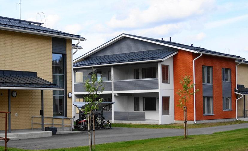 Kaksikerroksisia puna-keltatiilisiä taloja harmain puusomistein.