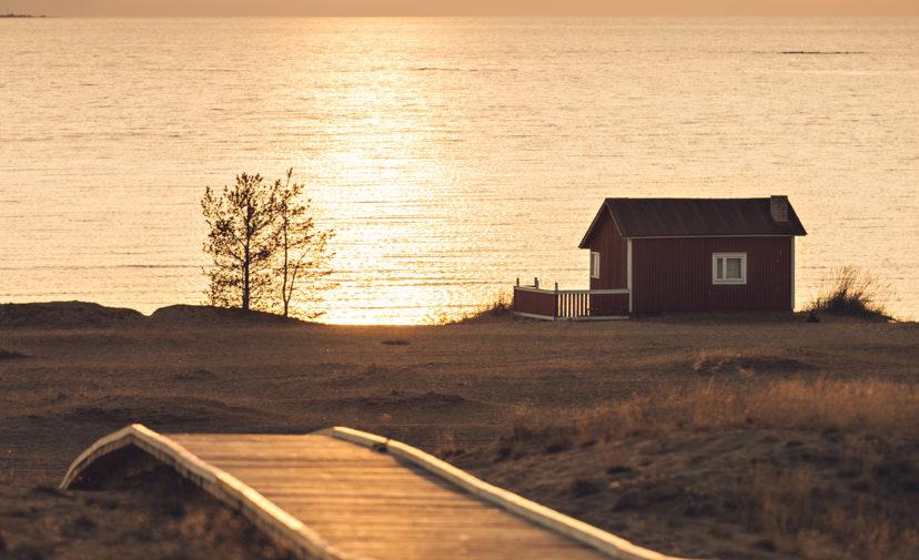 Merenranta ja mökki Hiekkasärkillä kesäisessä auringonlaskussa