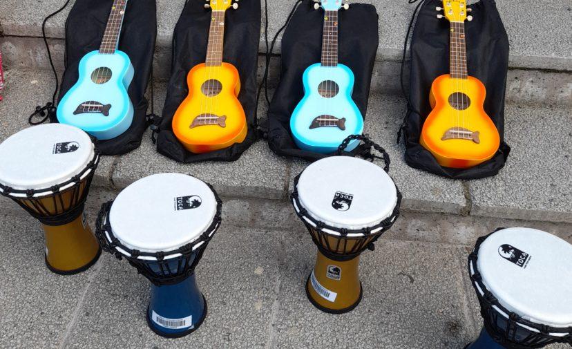 Betoniportailla turkooseja ja oransseja ukuleleja sekä djemne-rumpuja