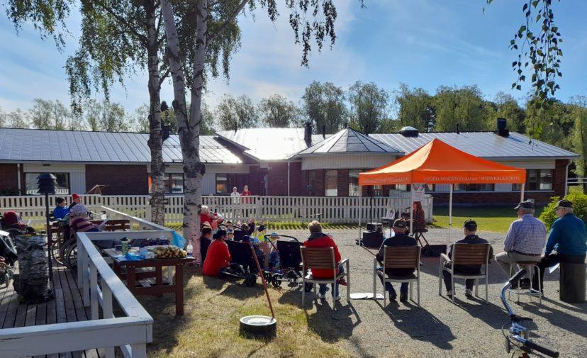 Ulkona aurinkoisessa säässsä ihmisiä ulkona tuoleilla istumassa, oranssi telttakatos, jonka alla kosketinsoittaja. Ruohikolla istumassa lapsia ja aikuisia