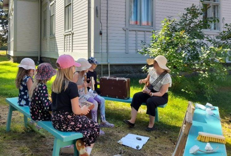 Pihalla kesällä turkooseilla penkeillä istumassa lapsia ja aikuinen soittamassa