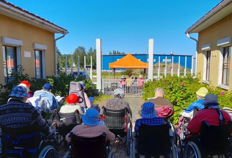 Ulkona aurinkoisessa säässä sisäpihalla ihmisiä istumassa selkä kameraan päin, taustalla oranssi teltta ja aita.